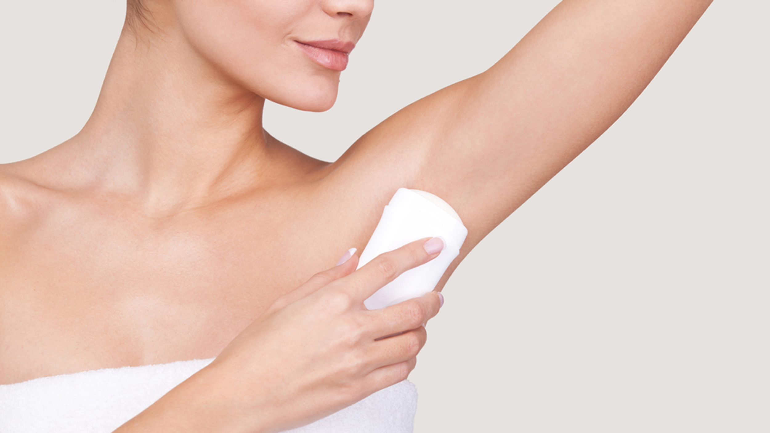 Staying fresh. Cropped image of beautiful young woman wrapped in towel standing against grey background, using deodorant; Shutterstock ID 171246548; PO: natural-deodorant-today-tease-160210; Client: TODAY Digital
